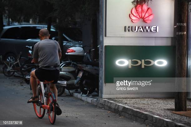 This photo taken on August 6 2018 shows a man cycling past signs of Huawei and Oppo outside a store selling mobile phones in Beijing Despite being...