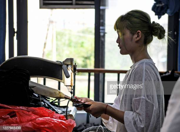 This photo taken on August 6, 2020 shows a worker producing shoes for export at a factory in Huainan in China's eastern Anhui province. - China saw...