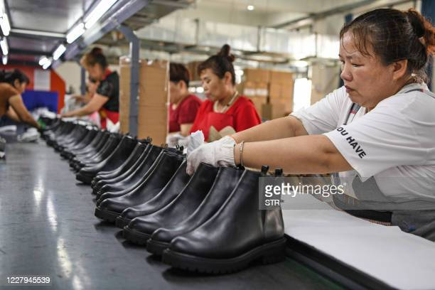 This photo taken on August 6, 2020 shows workers producing shoes for export at a factory in Huainan in China's eastern Anhui province. - China saw...