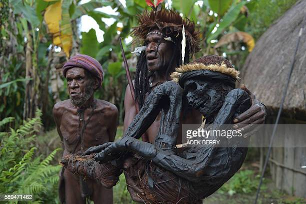 TOPSHOT This photo taken on August 7 2016 shows tribe chief Eli Mabel holding the mummified remains of his ancestor Agat Mamete Mabel in the village...
