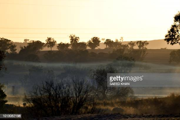 This photo taken on August 7 2018 shows the sun rising above dry farm paddocks in the droughthit area of Duri in New South Wales A crippling drought...