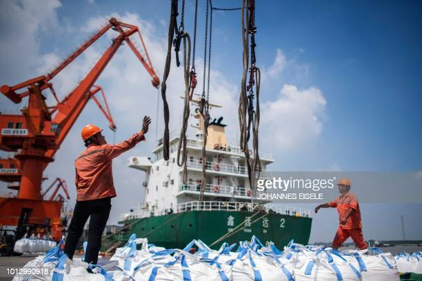This photo taken on August 7 2018 shows workers unloading bags of chemicals at a port in Zhangjiagang in China's eastern Jiangsu province China's...