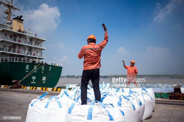This photo taken on August 7, 2018 shows workers unloading bags of chemicals at a port in Zhangjiagang in China's eastern Jiangsu province. - China's...
