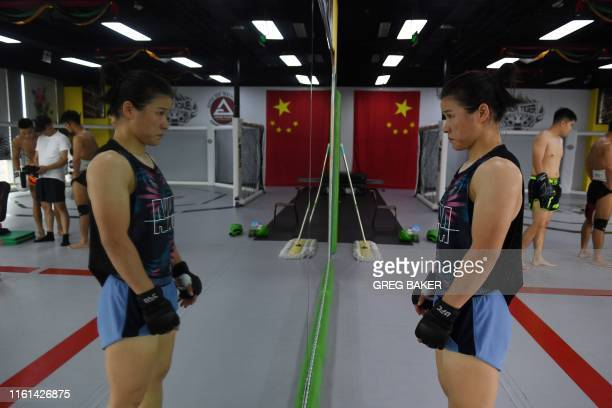 This photo taken on August 7 2019 shows Chinese mixed martial arts fighter Zhang Weili standing in front of a mirror during a training session in a...