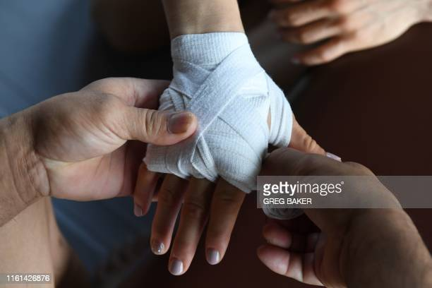 This photo taken on August 7 2019 shows Chinese mixed martial arts fighter Zhang Weili having her hands strapped before a training session in a gym...