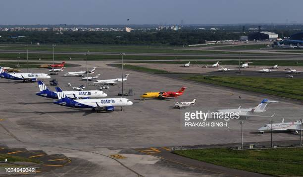 This photo taken on August 9 2018 shows aircraft of India's GoAir next to private jets at a parking bay at Indira Gandhi International Airport in New...