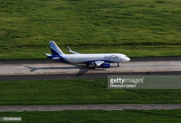 This photo taken on August 9 2018 shows an aircraft of India's IndiGo airline taxi on the runway prior to take off at Indira Gandhi International...