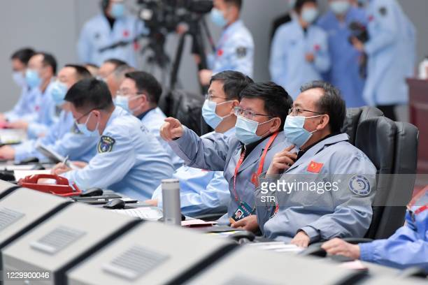 This photo taken on December 1, 2020 shows technical personnel monitoring the process during the Chang'e-5 lunar probe landing on the moon at the...