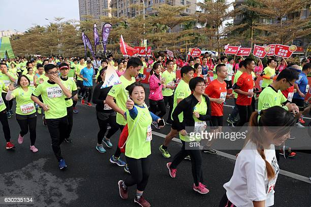 This photo taken on December 10 2016 shows runners taking part in the half marathon in Xiamen eastern China's Fujian province A runner who...