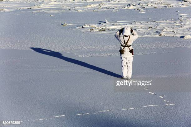 This photo taken on December 10 2017 shows a Chinese soldier looking over snow along the border with Russia in Heihe in China's northeastern...