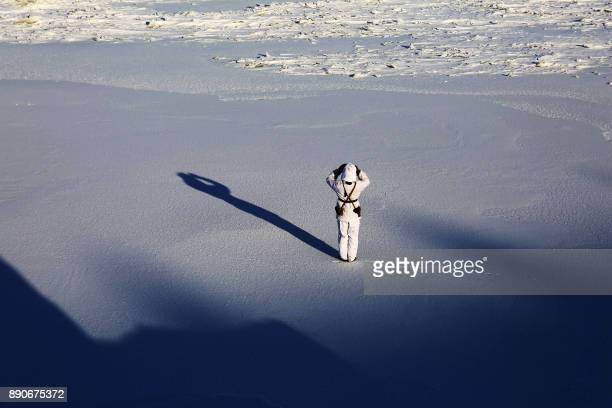 This photo taken on December 10 2017 shows a Chinese soldier standing guard over snow along the border with Russia in Heihe in China's northeastern...