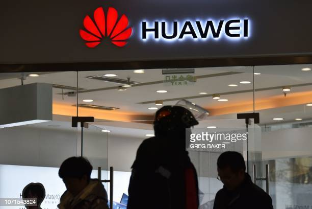 This photo taken on December 10 2018 shows people walking past a Huawei store in Beijing China's ambitious drive to dominate nextgeneration 5G...