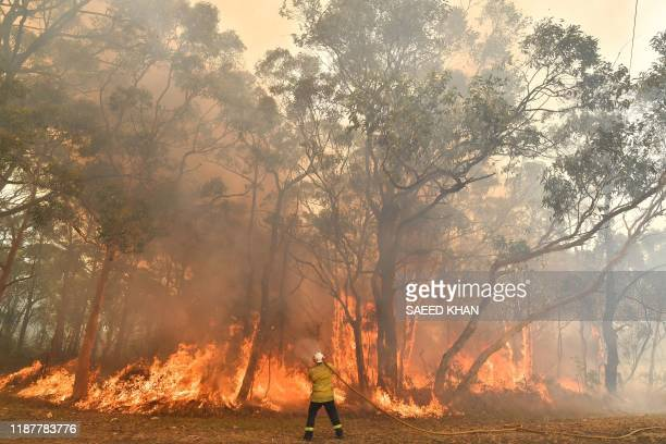 TOPSHOT This photo taken on December 10 2019 shows a firefighter conducting backburning measures to secure residential areas from encroaching...