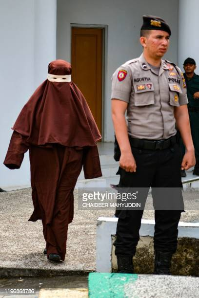 This photo taken on December 10, 2019 shows the first female flogger arriving to whip a woman in public, in Banda Aceh, after she was caught in close...