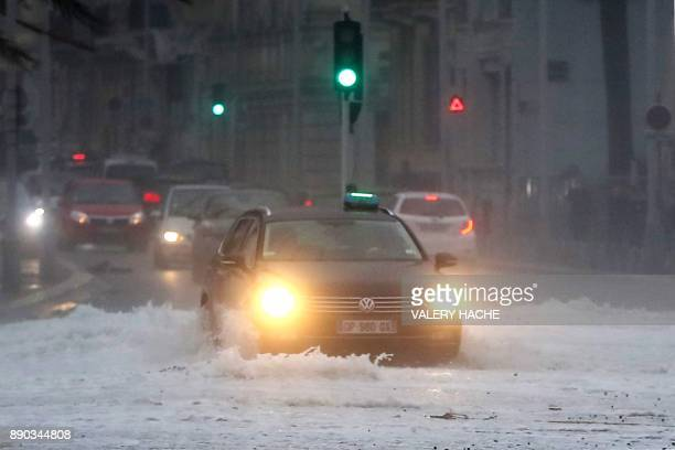 This photo taken on December 11, 2017 in Nice shows a car driving through flooded streets, as storm Ana smashes into France. The arrival of the storm...