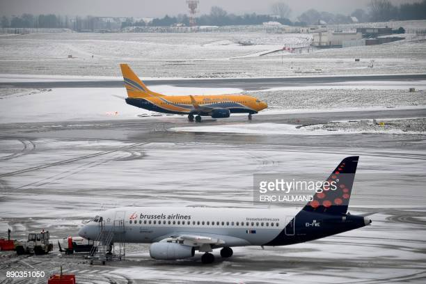 This photo taken on December 11 2017 shows an ASL Airlines Europe Airpost airplane and Brussels Airlines airplane on the tarmac of Brussels Airport...