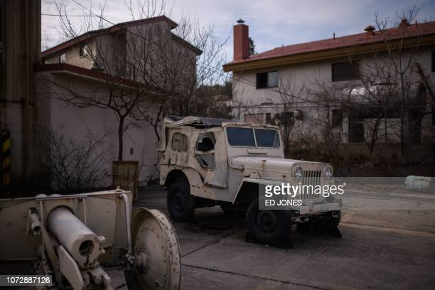 This photo taken on December 11 2018 shows a vehicle and decommissioned weapons before rundown accommodation blocks at Camp Greaves a former US army...