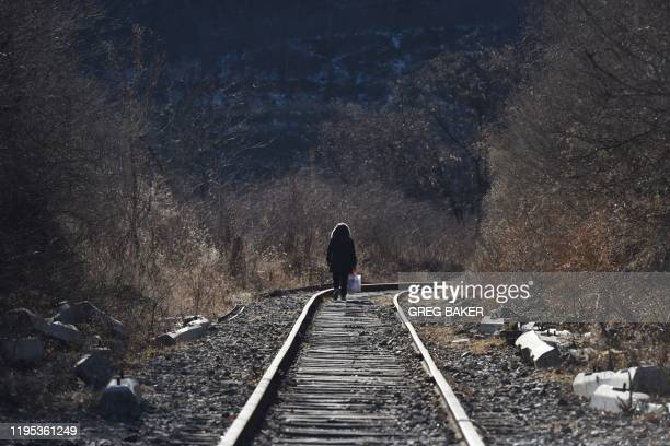 This photo taken on December 11 2019 shows a woman walking along a railway line near the Datai coal mine in Mentougou west of Beijing