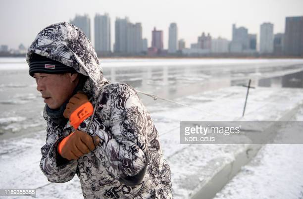 TOPSHOT This photo taken on December 11 2019 shows a worker dragging ice blocks on the frozen Songhua river in Harbin China's northeastern...