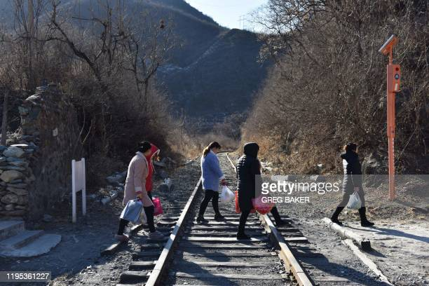 This photo taken on December 11 2019 shows residents crossing a railway line on the way back to their homes near the Datai coal mine in Mentougou...