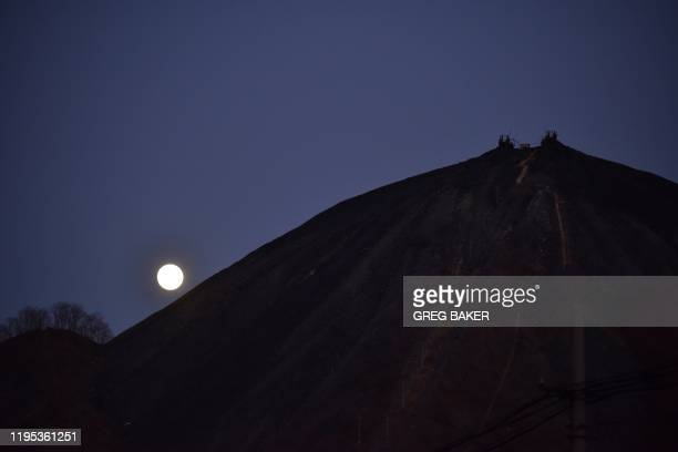 TOPSHOT This photo taken on December 11 2019 shows the moon rising behind mining equipment on a mountain of rocks at the Datai coal mine in Mentougou...