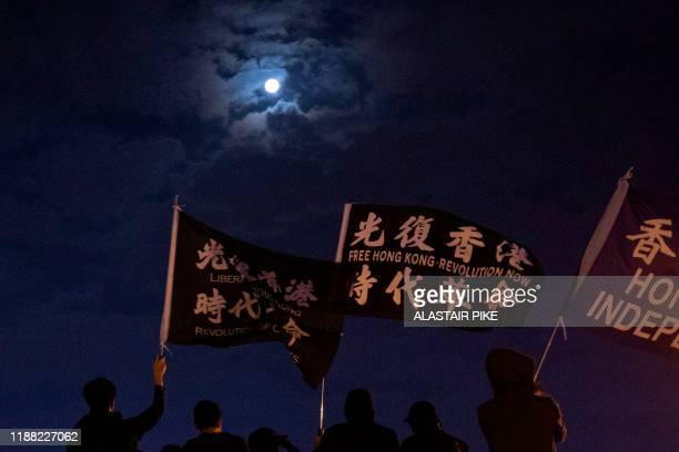 TOPSHOT This photo taken on December 12 2019 shows protesters waving black flags reading in Chinese liberate Hong Kong revolution of our times on a...