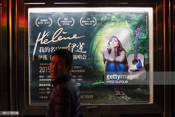 This photo taken on December 13 2015 shows a Chinese man standing next a poster of French actress and singer Hélène Rolles primarily known for her...