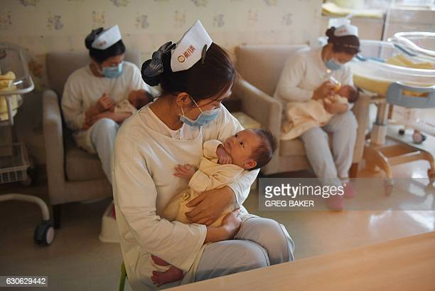 This photo taken on December 13 2016 shows nurses holding babies at the Xiyuege Centre or 'Lucky Month Home' in Beijing Since the late 70s strict...