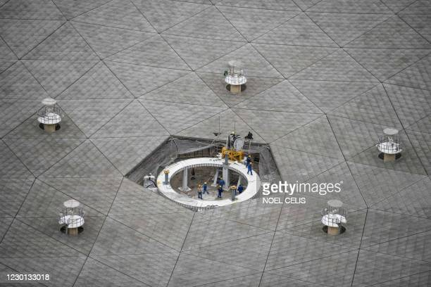 This photo taken on December 13 shows workers at the Five-hundred-meter Aperture Spherical radio Telescope conducting maintenance at the National...