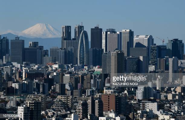 This photo taken on December 14, 2018 shows a snow-capped Mount Fuji in the distance, pictured from the observation deck of a skyscraper in Tokyo. -...