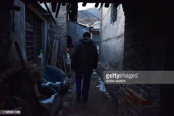 This photo taken on December 18 2019 shows a former coal miner walking to his home in a village outside the Datai coal mine in Mentougou west of...