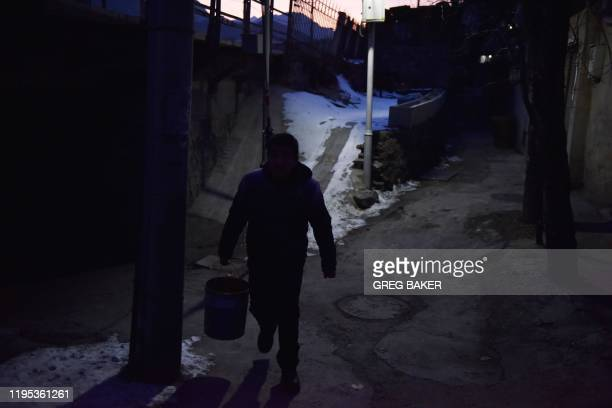 This photo taken on December 18 2019 shows a man walking through a village outside the Datai coal mine in Mentougou west of Beijing