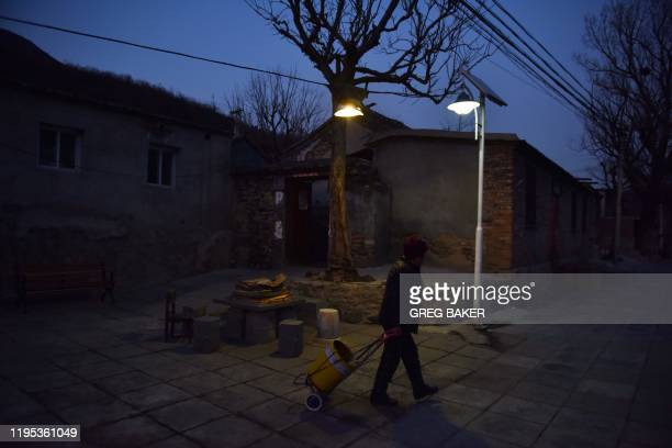 This photo taken on December 18 2019 shows a woman walking through a village outside the Datai coal mine in Mentougou west of Beijing