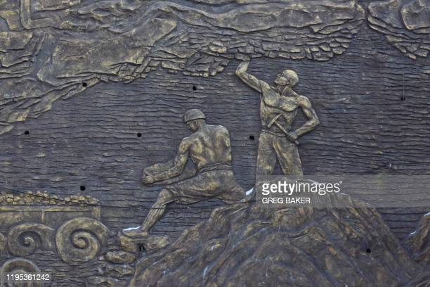 This photo taken on December 18 2019 shows an art work depicting coal miners at a museum outside the closed Muchengjian coal mine in Mentougou west...