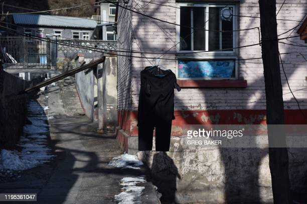 This photo taken on December 18 2019 shows clothes drying outside home next to the Datai coal mine in Mentougou west of Beijing