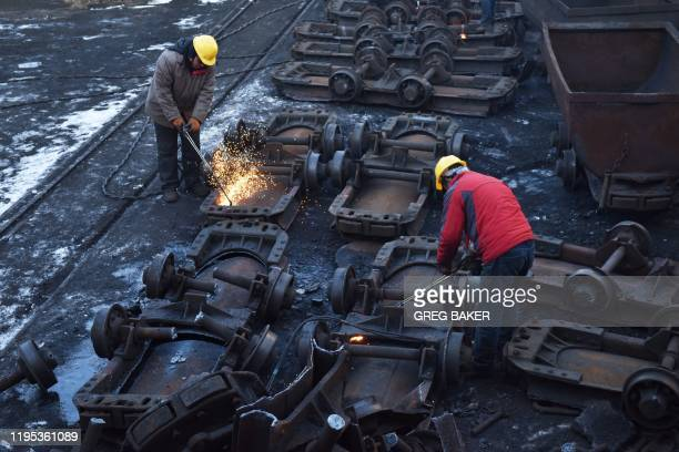 This photo taken on December 18 2019 shows workers cutting up coal carts at the Datai coal mine in Mentougou west of Beijing