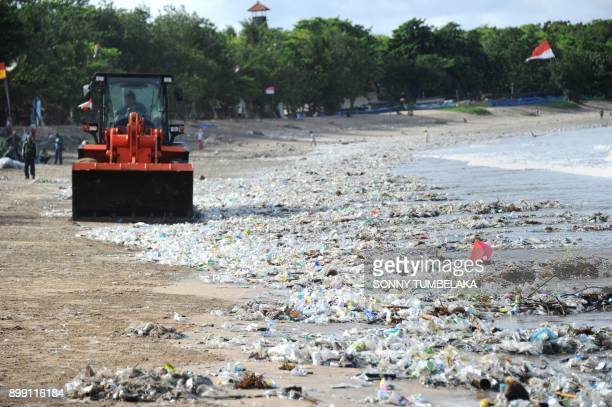 This photo taken on December 19 2017 shows rubbish collectors using heavy equipment to clear plastic trash on Kuta beach near Denpasar on Indonesia's...