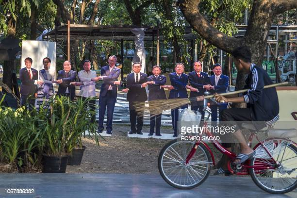 This photo taken on December 2 2018 shows a worker cycling past lifesize portraits of the 10 leaders of the Association of Southeast Asian Nations...