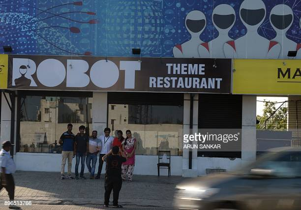 This photo taken on December 20 2017 shows Indian visitors taking photos outside of a robotthemed restaurant in Chennai India's first robotthemed...