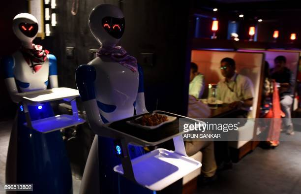 This photo taken on December 20 2017 shows robot waiters carrying food for Indian customers at a robotthemed restaurant in Chennai India's first...