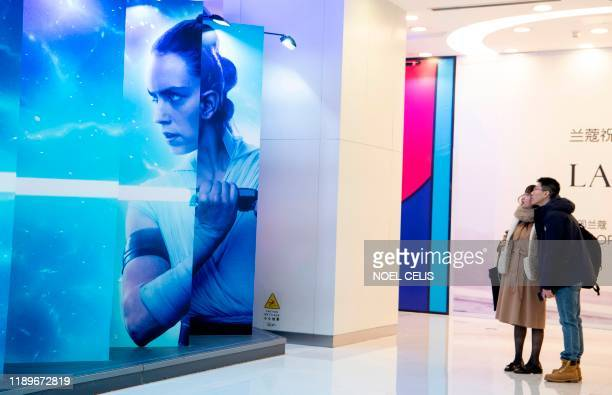This photo taken on December 20 2019 shows a couple looking at a promotional installation for the latest Star Wars movie The Rise of Skywalker at a...