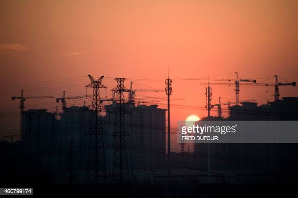 This photo taken on December 22 2014 shows construction cranes rising from a housing development behind a line of electrical pylons near Hengshui in...