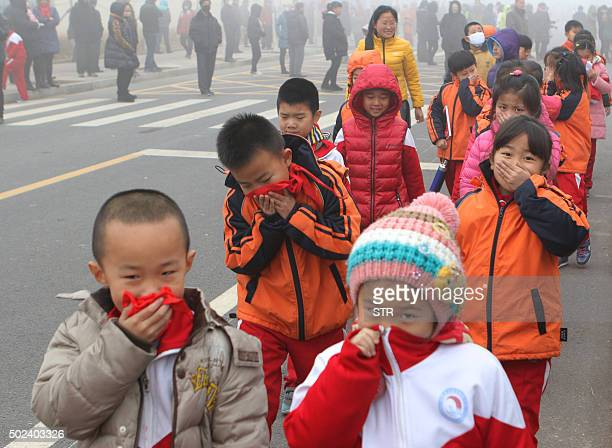 This photo taken on December 23 2015 shows pupils from an elementary school covering their mouths and noses as they leave the schoolyard after the...