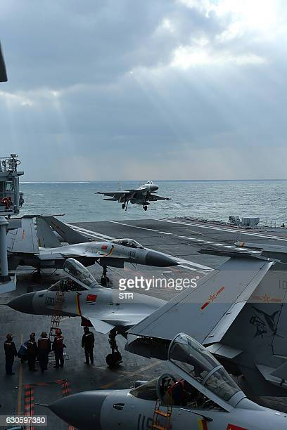 This photo taken on December 23 2016 shows Chinese J15 fighter jets on the deck of the Liaoning aircraft carrier during military drills in the Yellow...