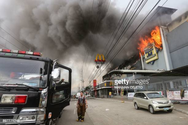 TOPSHOT This photo taken on December 23 2017 shows a firefighter standing in front of a burning shopping mall in Davao City on the southern...