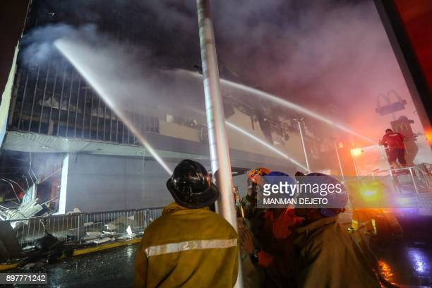 This photo taken on December 23 2017 shows firefighters extinguishing a fire at a shopping mall in Davao City on the southern Philippine island of...