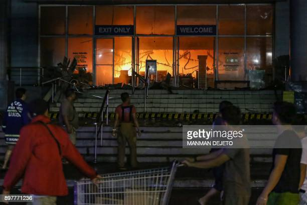 This photo taken on December 23 2017 shows people looking at a fire at a shopping mall in Davao City on the southern Philippine island of Mindanao...