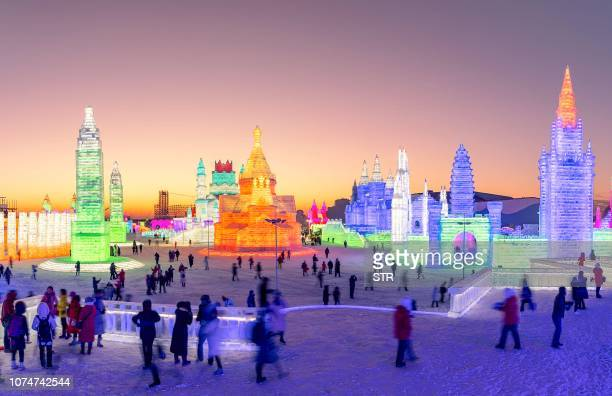 TOPSHOT This photo taken on December 23 2018 shows people visiting the Harbin IceSnow World in Harbin China's northeastern Heilongjiang province The...