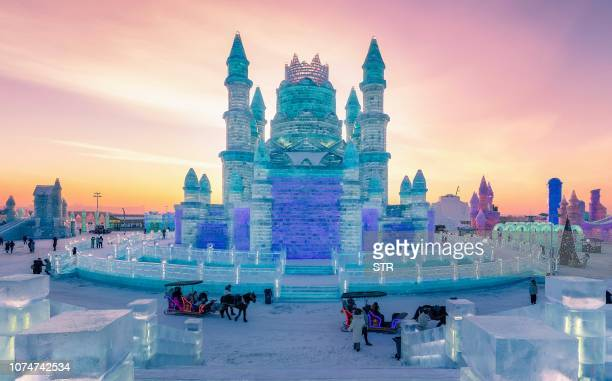 TOPSHOT This photo taken on December 24 2018 shows people visiting the Harbin IceSnow World in Harbin China's northeastern Heilongjiang province The...