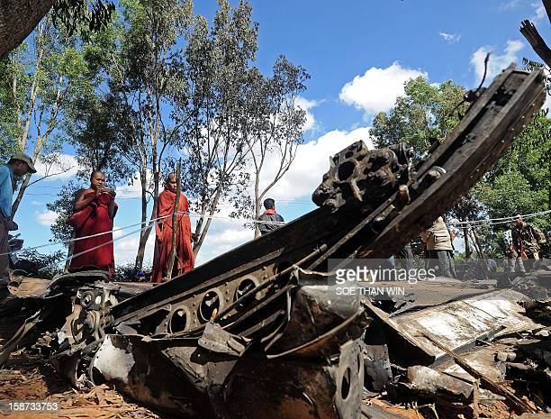 This photo taken on December 26 2012 shows Buddhist monks taking pictures of debris from an Air Bagan plane that crash landed the day before near...